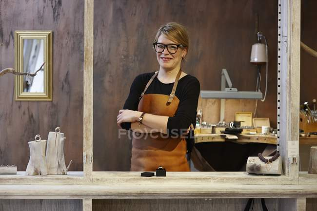 Portrait of smiling goldsmith in her shop, smiling at camera with hands crossed — Stock Photo