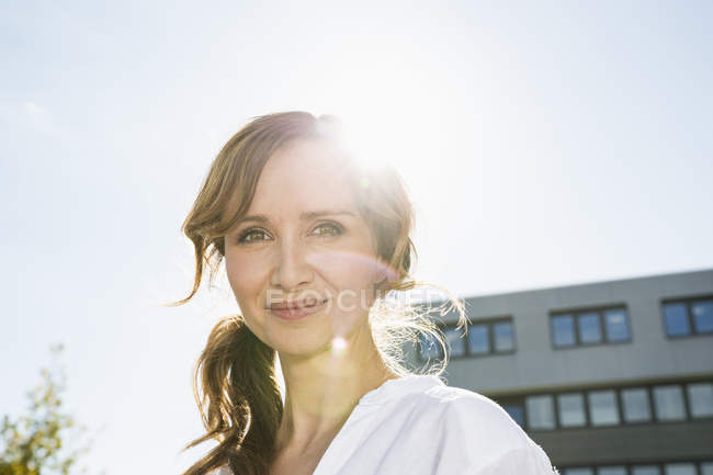 Portrait of smiling businesswoman at backlight — Stock Photo