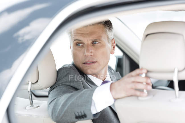 Businessman driving car turning round — Stock Photo