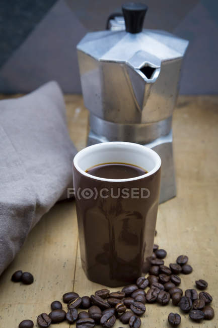 Cup of coffee, cloth, espresso can and coffee beans — Stock Photo