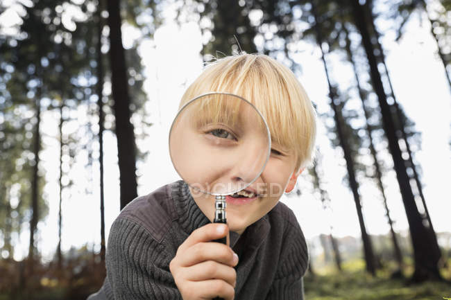 Little boy looking through magnifying glass at viewer — Stock Photo