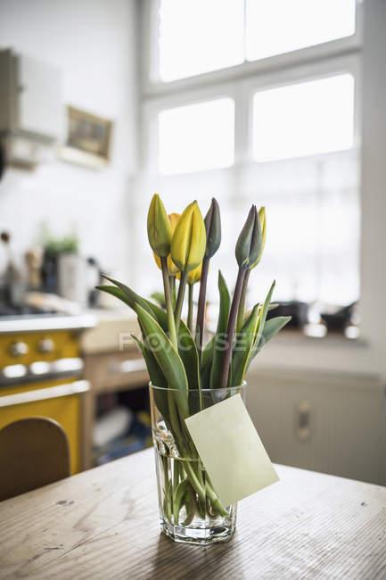 Клейкие записки наклеивания на стекло с тюльпанами на кухонном столе — стоковое фото