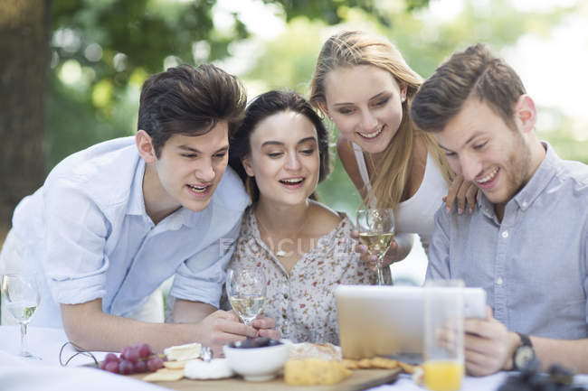 Друзі, їдальня і на відкритому повітрі використанням цифровий планшетний — стокове фото