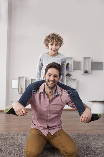 Батько несучи сина на плечах — стокове фото