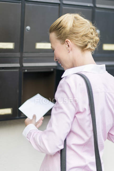 Woman standing in front of mailbox watching letter — Stock Photo