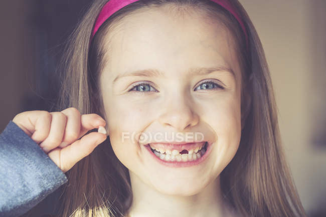 Portrait of smiling little girl with tooth gap holding milk tooth in hand — Stock Photo