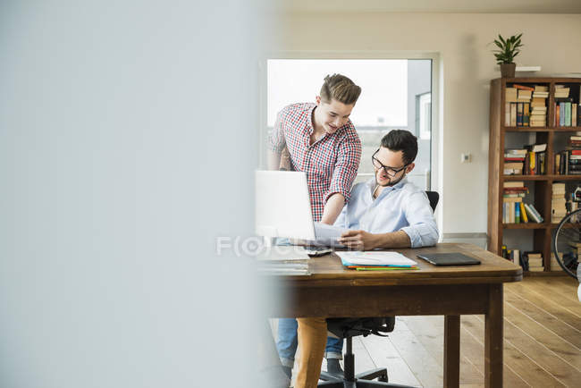 Two smiling young men talking at desk with documents and laptop — Stock Photo