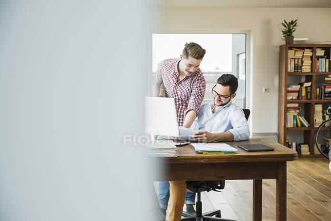 Dois jovens sorridentes conversando na mesa com documentos e laptop — Fotografia de Stock