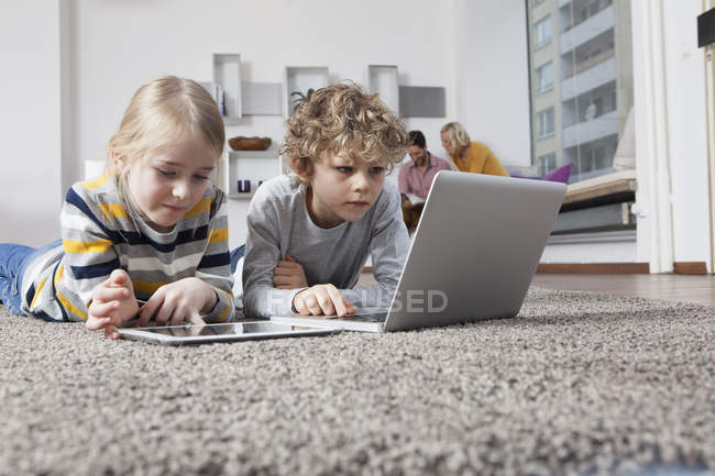 Bruder und Schwester am Boden liegend mit Laptop und digitalem Tablet — Stockfoto