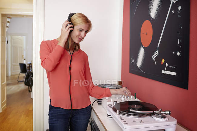 Smiling young woman with headphones, record player and mixing console at home — Stock Photo