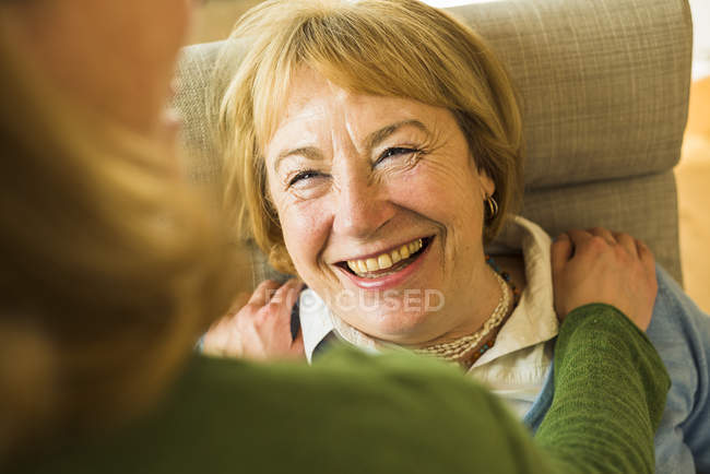 Smiling grandmother looking at adult granddaughter — Stock Photo