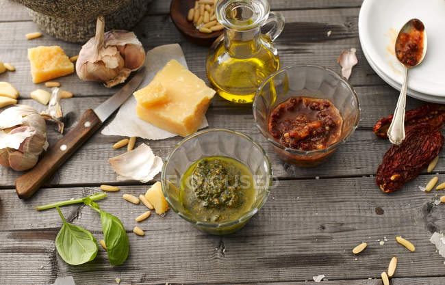 Glass bowls of homemade basil and tomato pesto and ingredients — Stock Photo