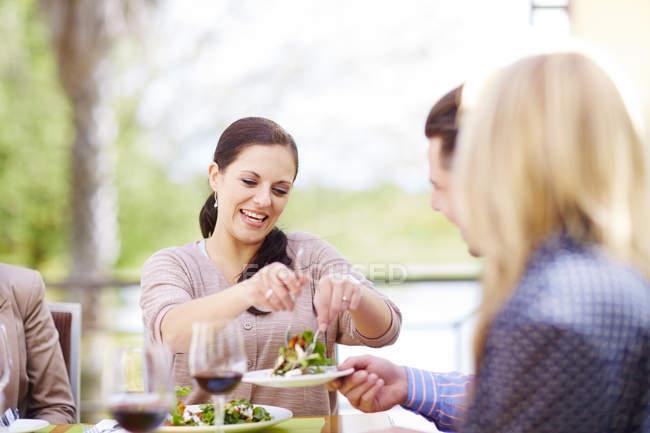 Amigos que tienen ensalada y vino tinto en logia - foto de stock