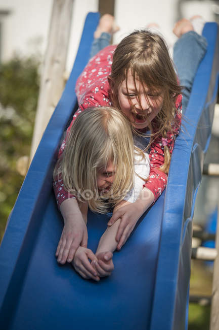 Two happy girls having fun on a slide — Stock Photo