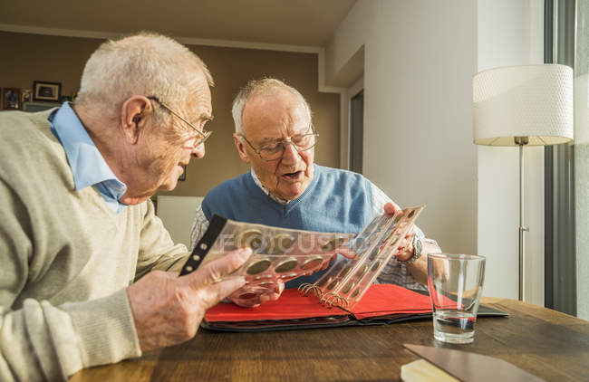 Two senior friends with coin album at home — Stock Photo