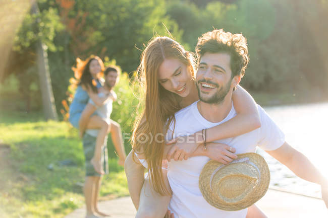 Happy young man carrying girlfriend piggyback — Stock Photo