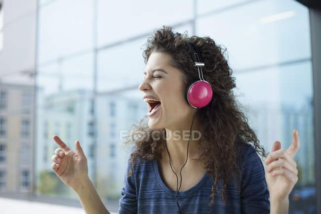 Gritando jovem mulher usando fones de ouvido na janela — Fotografia de Stock