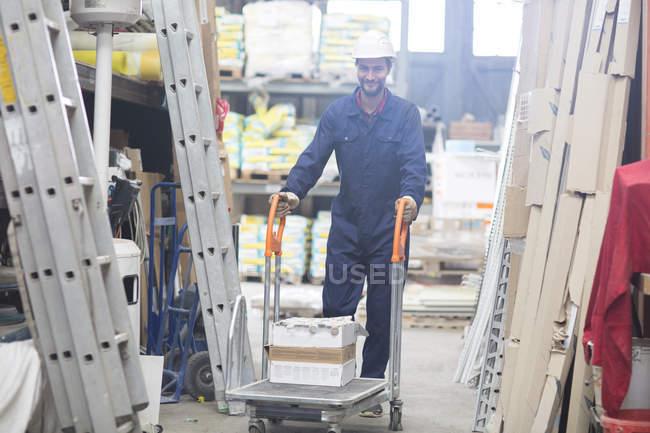 Manutentionnaire dans l'entrepôt en poussant le chariot — Photo de stock