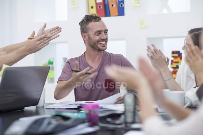 Gens de bureau créatif applaudissant leur collègue — Photo de stock