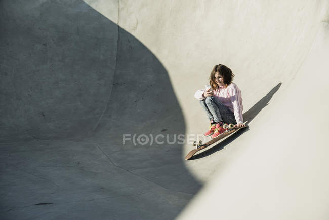 Mädchen im Skatepark sitzen über Rampe — Stockfoto