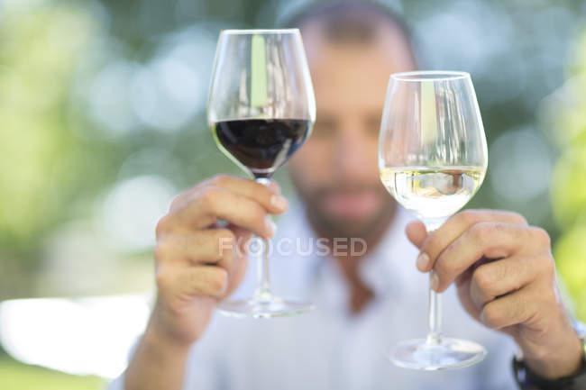Человек, сравнивая вино белое и красное вино на дегустацию сессии — стоковое фото
