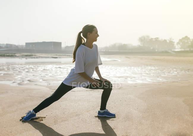 Giovane donna che si estende sulla spiaggia — Foto stock