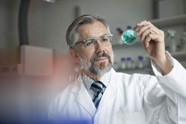 Scientist in laboratory examining liquid in round bottom flask — Stock Photo