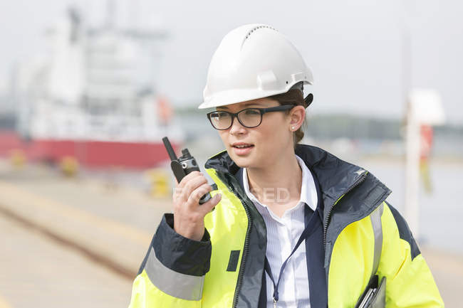 Woman with walkie-talkie at container port — Stock Photo