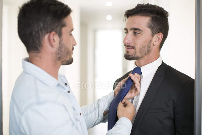 Casually dressed man adjusting tie of twin brother in office — Stock Photo