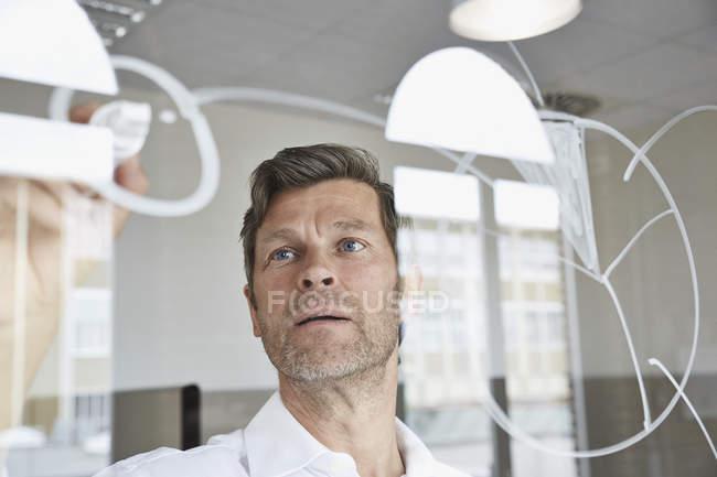 Disegno Di Ufficio : Uomo d affari disegno di diagrammi su lastra di vetro in ufficio