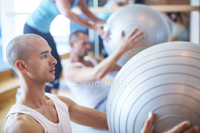 Young man with gymnastics ball in the gym — Stock Photo