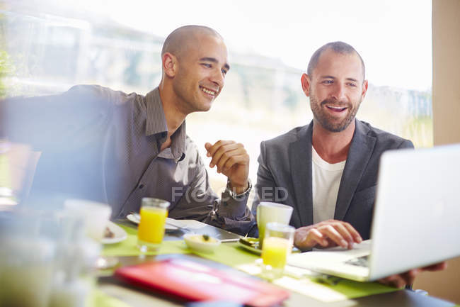 Two businessmen with laptop at dining table — Stock Photo