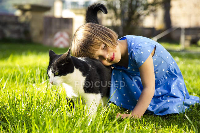 Little girl with cat on a meadow — Stock Photo