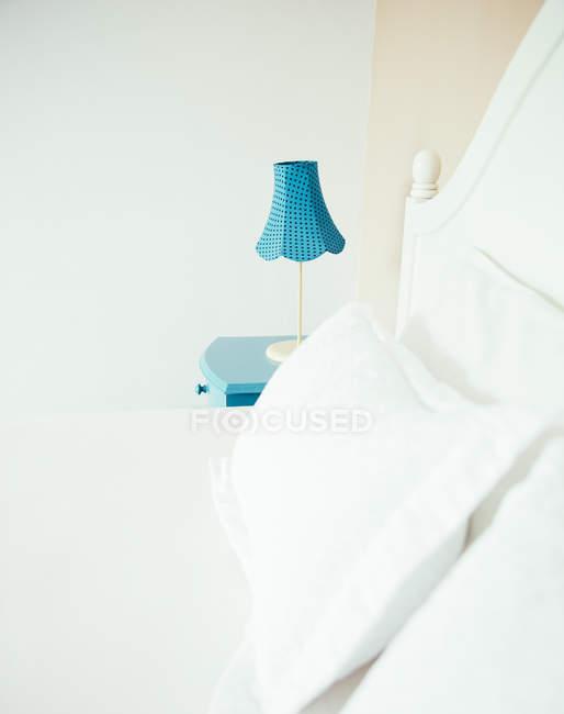 Indonésia, Bali, candeeiro de mesa na cabeceira azul do armário e cama no quarto de uma casa de férias — Fotografia de Stock
