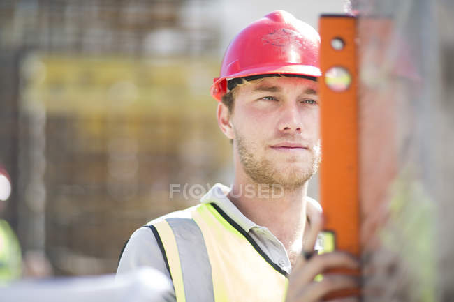 Рабочий-строитель, использующий спиртовой уровень — стоковое фото