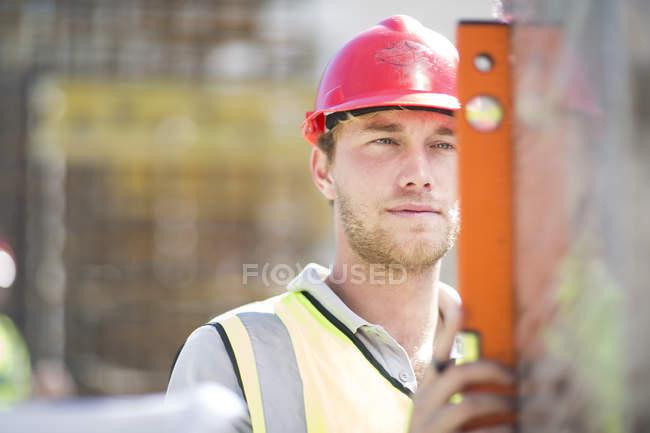 Bauarbeiter mit Wasserwaage — Stockfoto