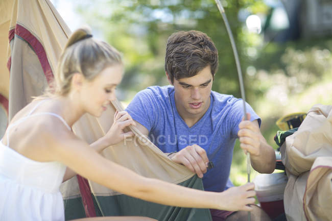 Young couple setting up a tent together outdoors — Stock Photo