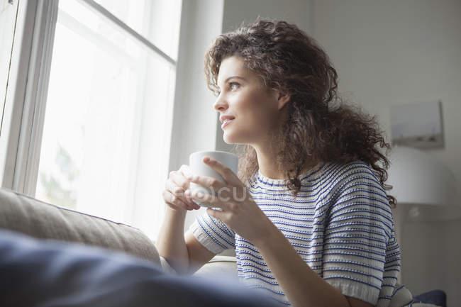 Улыбающаяся молодая женщина с чашкой кофе смотрит в окно — стоковое фото