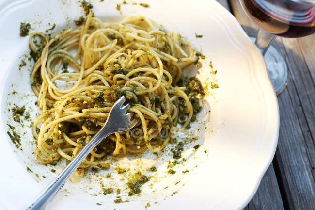 Gabel in Spaghetti-Teller serviert mit Basilikum-pesto — Stockfoto