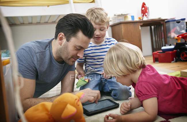 Father and children using tablet — Stock Photo