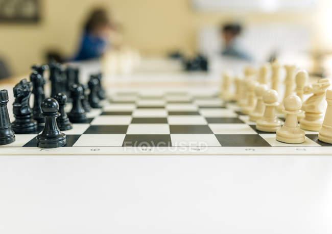 Juego de ajedrez en la mesa con niños jugando en segundo plano - foto de stock
