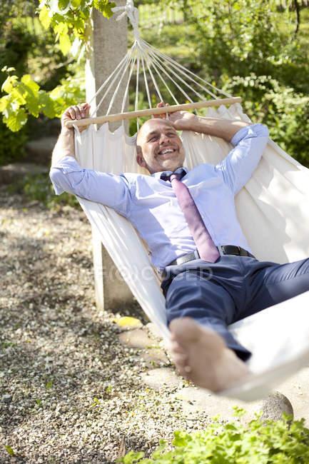 Empresário relaxante em rede em um jardim — Fotografia de Stock