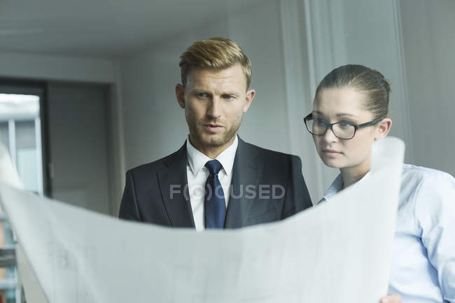 Business people holing construction plan — Stock Photo
