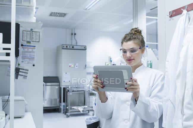 Scientifique en laboratoire tenant une tablette numérique — Photo de stock