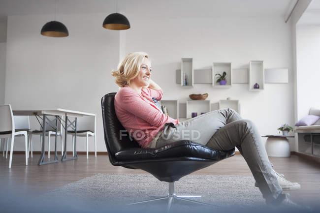 Mulher, relaxante na poltrona de couro em casa — Fotografia de Stock