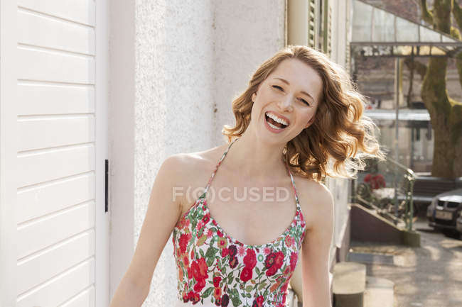 Portrait of laughing young woman with curly hair — Stock Photo