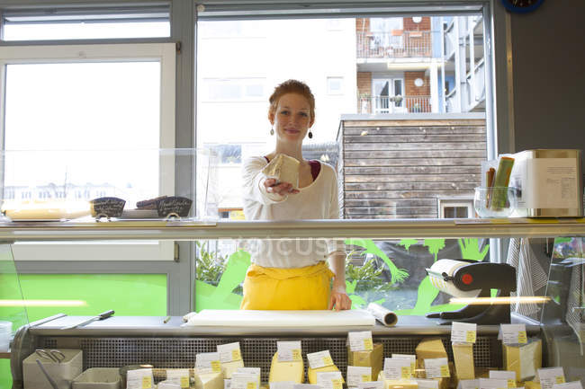 Smiling young woman in wholefood shop giving piece of cheese — Stock Photo