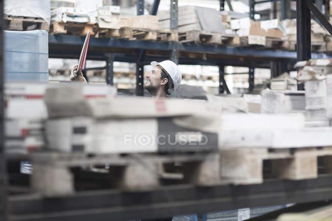 Хранитель на складе среди стеллажей — стоковое фото