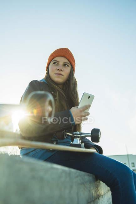 Fille avec téléphone cellulaire au skatepark — Photo de stock