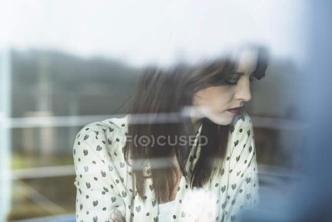 Giovane donna dietro il vetro della finestra — Foto stock